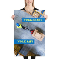 A safety poster showing a bird's-eye view of a worker in a warehouse pulling boxes on a pallet jack with the slogan work smart, work safe.