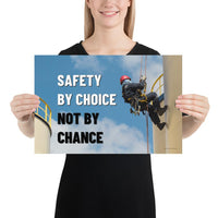 A fully harnessed man wearing a hard hat scaling the side of a building with a bright blue sky and clouds in the background with the text safety by choice, not by chance in bold text to his left.-Poster-12×18