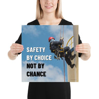 A fully harnessed man wearing a hard hat scaling the side of a building with a bright blue sky and clouds in the background with the text safety by choice, not by chance in bold text to his left.-Poster-16×16