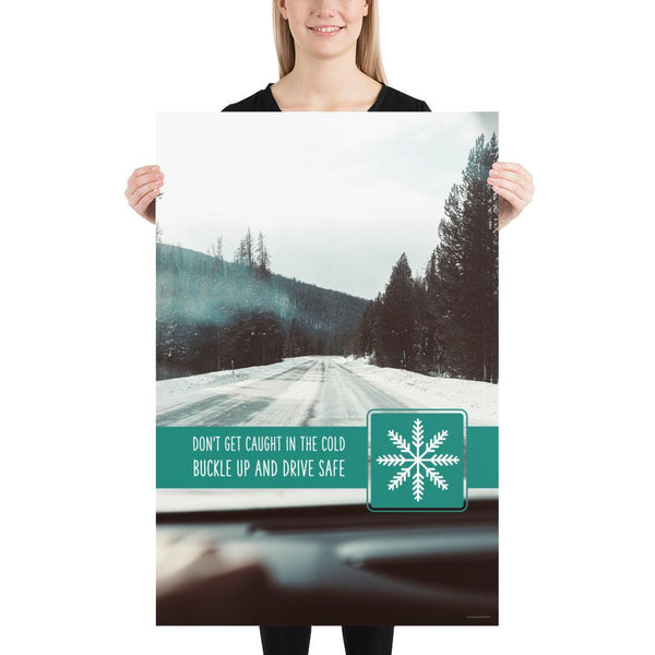 A safety poster showing a picture taken from the dashboard of a car showing an iced over road in the mountains with the slogan don't get caught in the cold, buckle up and stay safe.