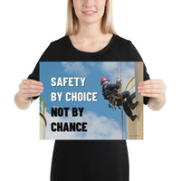 A fully harnessed man wearing a hard hat scaling the side of a building with a bright blue sky and clouds in the background with the text safety by choice, not by chance in bold text to his left.-Poster-12×16