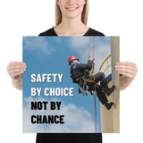 A fully harnessed man wearing a hard hat scaling the side of a building with a bright blue sky and clouds in the background with the text safety by choice, not by chance in bold text to his left.-Poster-18×18
