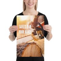 A safety poster showing a close-up of a man's hands holding a chainsaw sawing through a log with sawdust flying everywhere with the text safety is in your hands to the left.