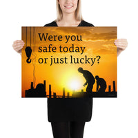 A workplace safety poster showing workers on a construction site being silhouetted in black with a sunset of orange hues in the background with the slogan were you safe today, or just lucky?
