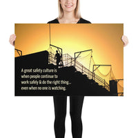 A construction safety poster showing the silhouette of a construction worker working on a building with a bright yellow sunset in the background and a safety slogan in the bottom left corner.