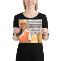 Safety poster showing a female warehouse worker smiling and wearing an orange reflective safety vest and orange hard hat with a safety quote written in dark text.