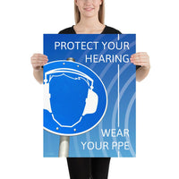 A hearing protection poster showing a bright blue construction sign with an illustration of a face wearing ear muffs with sound waves coming from the right and a safety slogan in the upper right and bottom right corners.
