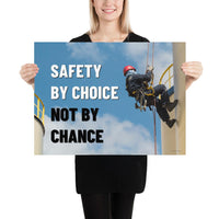 A fully harnessed man wearing a hard hat scaling the side of a building with a bright blue sky and clouds in the background with the text safety by choice, not by chance in bold text to his left.-Poster-18×24