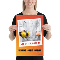 A hearing protection poster showing a doctor in a white lab coat holding out ear muffs in one hand and ear plugs in the other with a safety slogan below.