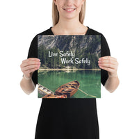 A workplace safety poster depicting a beautiful landscape of mountains in the background of a lake with a little wooden boat in the lake with text saying live safely work safely.