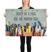 A workplace safety poster showing various tools such as a screwdriver, wrench, and pliers on a wooden table with the slogan don't be a fool use the proper tool.