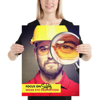 An eye safety poster showing a close up of a man's face wearing safety glasses and a yellow hard hat with a magnifying glass focusing on the right eye with an eye safety slogan underneath him.