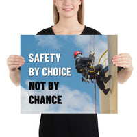 A fully harnessed man wearing a hard hat scaling the side of a building with a bright blue sky and clouds in the background with the text safety by choice, not by chance in bold text to his left.-Poster-16×20