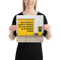 Workplace safety poster depicting a bright yellow garage door to a warehouse with a bold safety slogan on it with a smaller yellow door to the right.