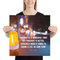 A workplace safety poster depicting a bright orange construction traffic light in the foreground of a blurry nighttime cityscape with a safety quote by William Blake.