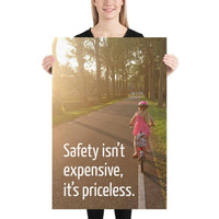 A safety poster showing a little girl riding her bike down a road on a sunny day with the slogan safety isn't expensive, it's priceless.