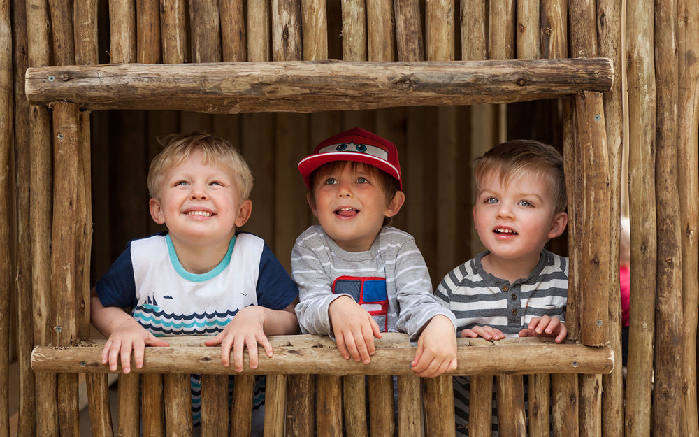 3 preschool boys smiling from a wooden playhouse at A pot full of colourful felt tip pens at Tadpoles Early Childhood Centre