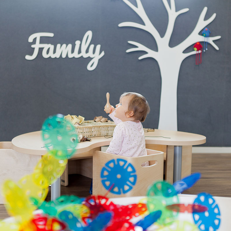 A little baby sitting at a table playing with rattle. The word Family appears on the wall at A pot full of colourful felt tip pens at Tadpoles Early Childhood Centre
