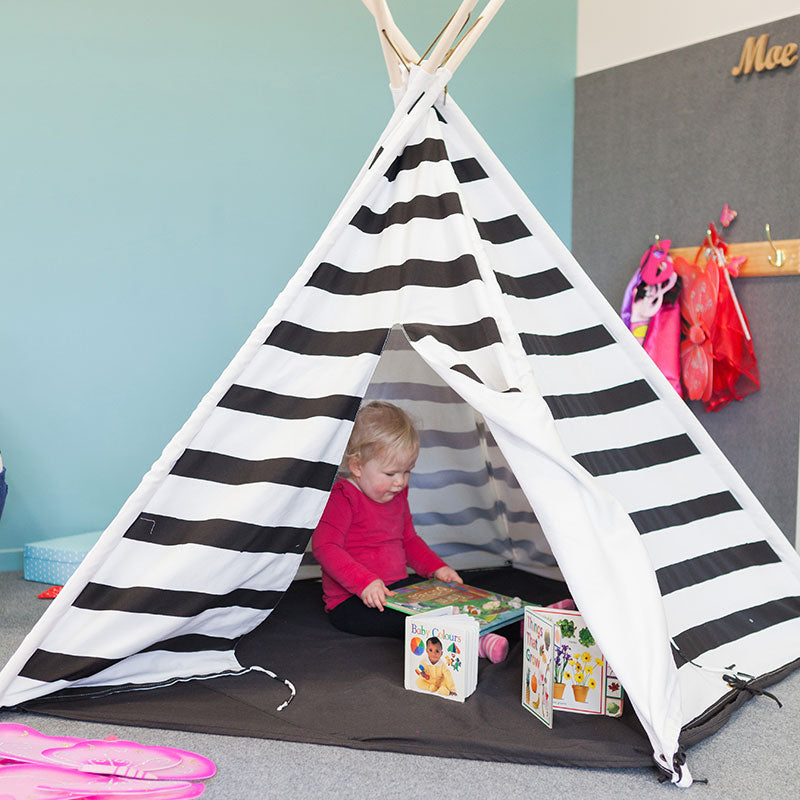 A little girl playing in a black and white striped tee pee at A pot full of colourful felt tip pens at Tadpoles Early Childhood Centre