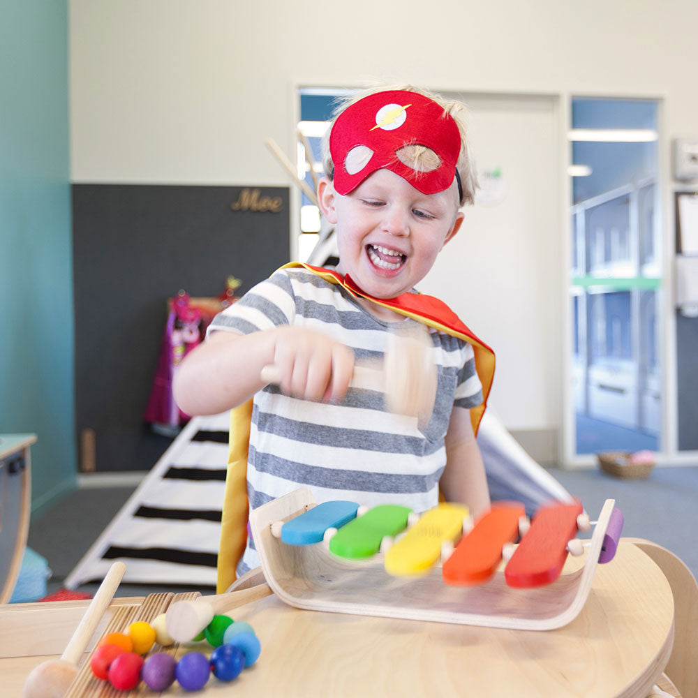 A little boy with a red mask hammering a wooden xylophone at A pot full of colourful felt tip pens at Tadpoles Early Childhood Centre