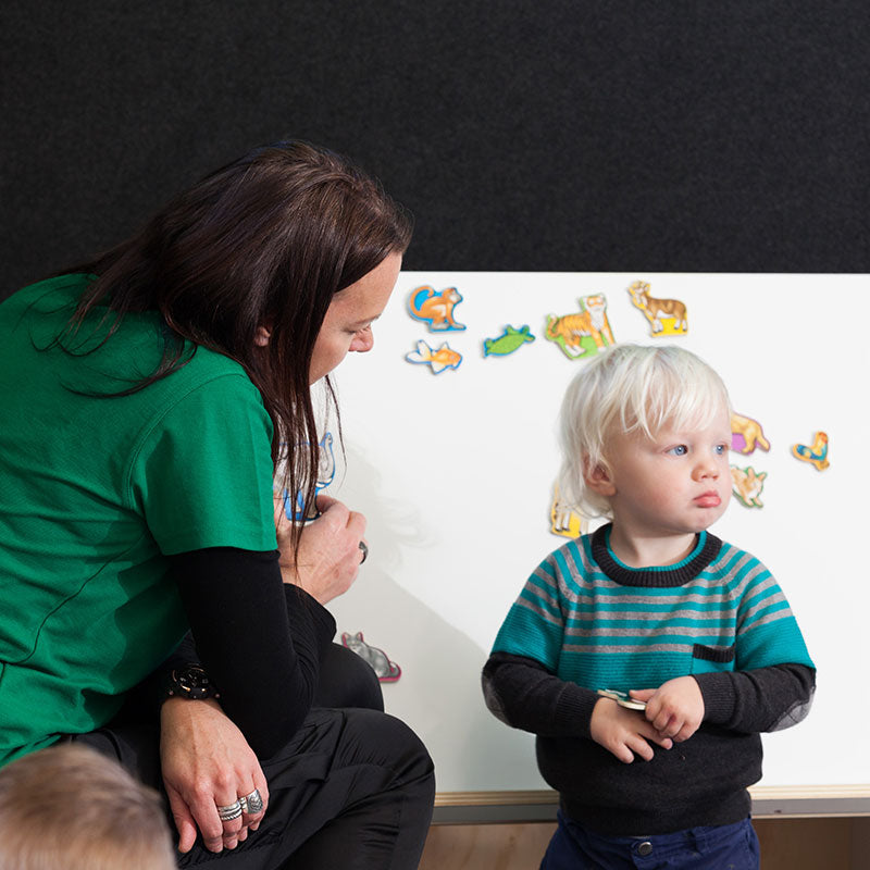 A teacher talking to a small boy at a whiteboard at A pot full of colourful felt tip pens at Tadpoles Early Childhood Centre