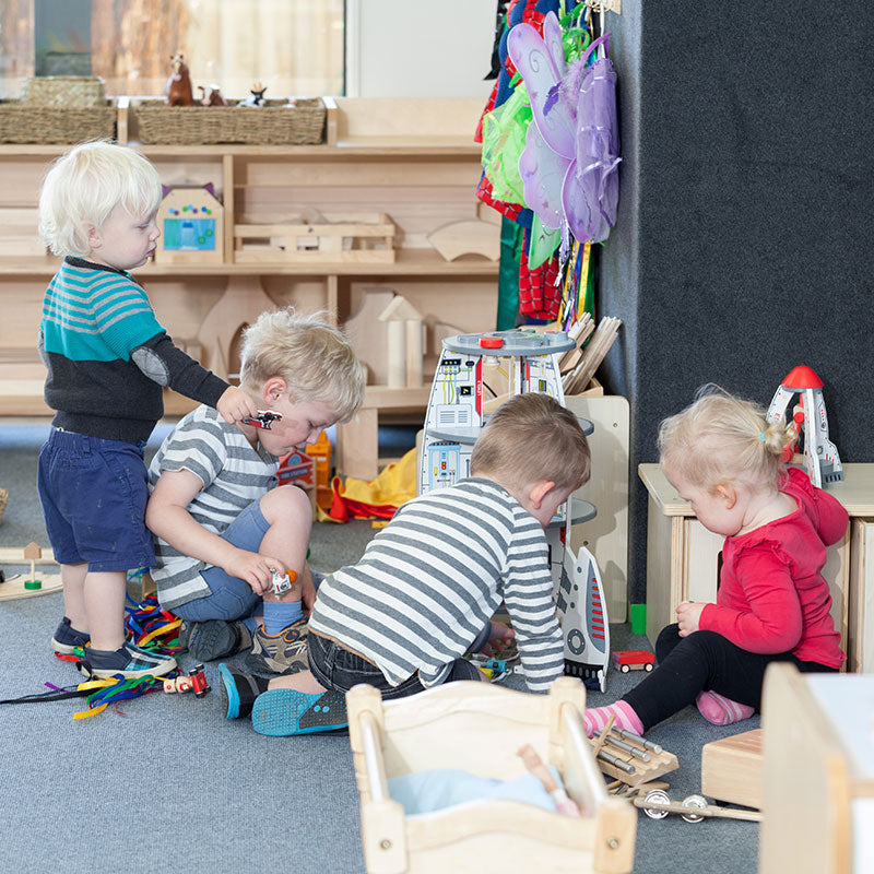 A group of children playing with toys on the ground at A pot full of colourful felt tip pens at Tadpoles Early Childhood Centre