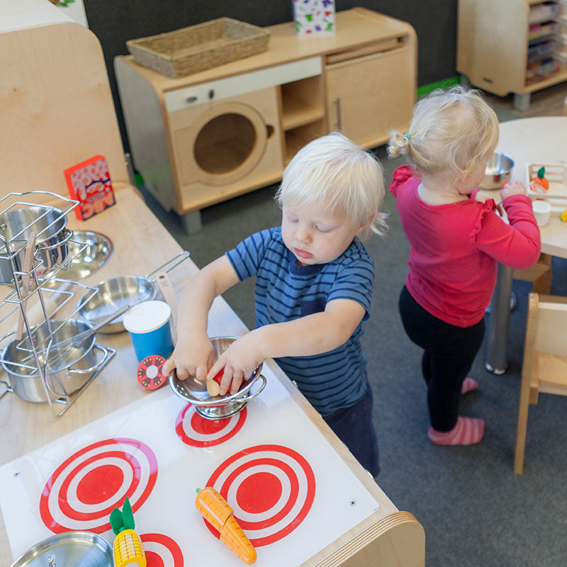 A boy and girl playing with a toy stove at A pot full of colourful felt tip pens at Tadpoles Early Childhood Centre