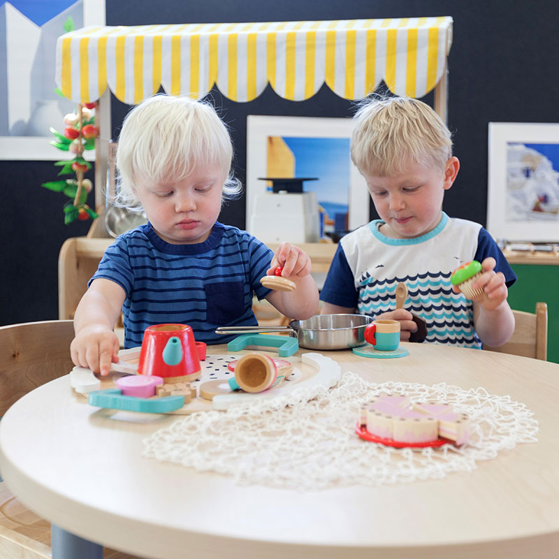 Two boys sitting at a table playing with toys at A pot full of colourful felt tip pens at Tadpoles Early Childhood Centre