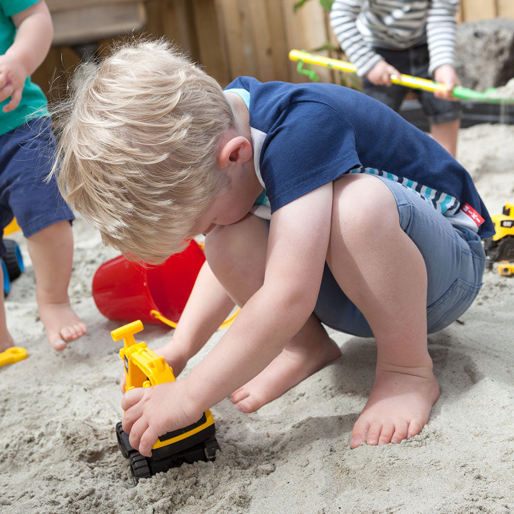 A little boy playing with a yellow digger in a sandpit at A pot full of colourful felt tip pens at Tadpoles Early Childhood Centre