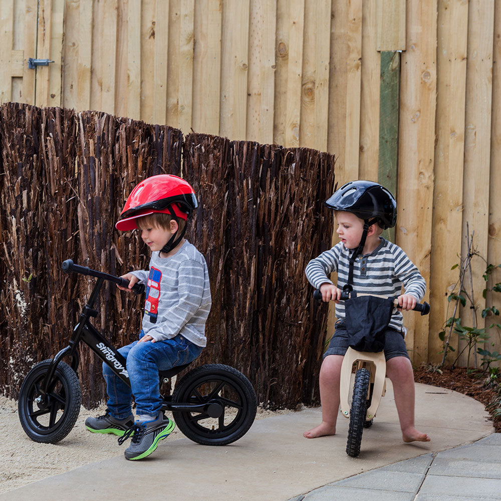 Two boys with helmets riding on bikes at A pot full of colourful felt tip pens at Tadpoles Early Childhood Centre