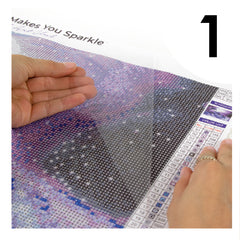 Hand pulling plastic film from diamond art canvas