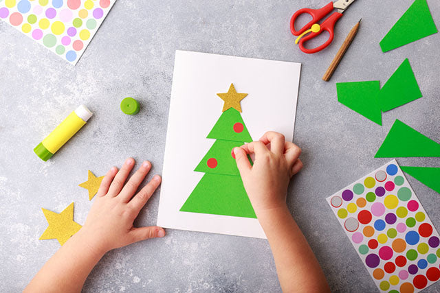 child makes a greeting card for christmas