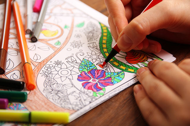 a person coloring using a soft tipped marker