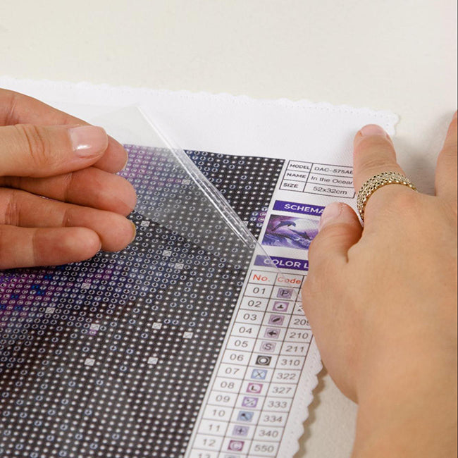 a person using a dmc color chart to cross reference diamonds