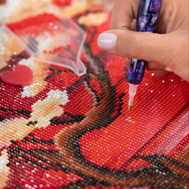 a person doing a diamond painting of a flower against a red background