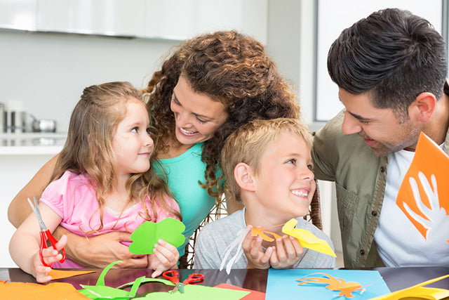 smiling young family doing arts and crafts