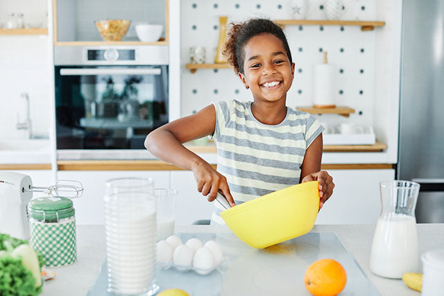a young girl using a mixing bowl in a kitchen
