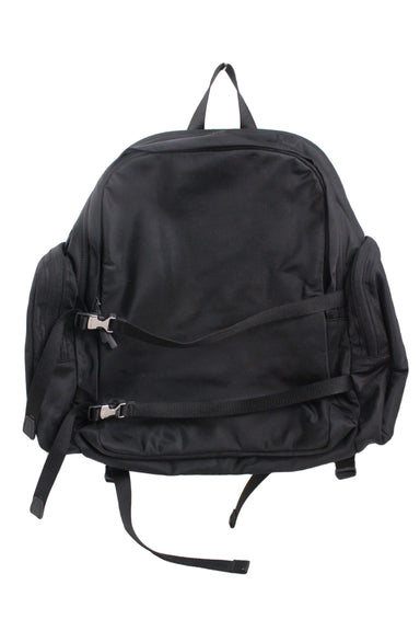 calvin klein black nylon wide backpack. features zippered pouch pockets at sides and adjustable, 2-strap front detail with silver-toned buckle closures. cushioned shoulder straps and backing with zippered laptop compartment; 2 inner wall pouch pockets, 1 zippered wall pocket. lined