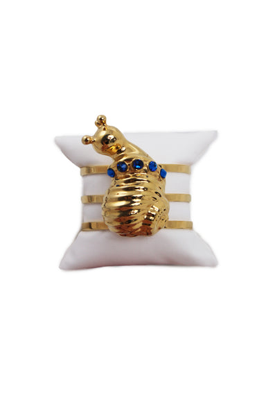 eva segoura gold tone snail cuff bracelet. features gold tone cutout band with cuff opening and tonal snail pendant with five blue swarovski crystals.