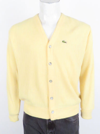 vintage lacoste v-neck cardigan. features lacoste crocodile logo patch at left breast. front button closure.