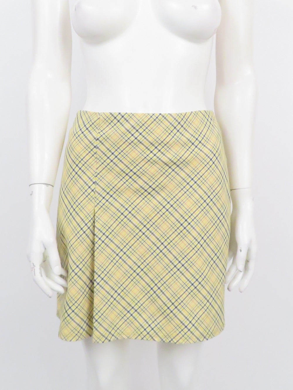 random pieces yellow plaid mini skirt. features diagonal plaid print. zipper at back middle. single pleat on left side front.