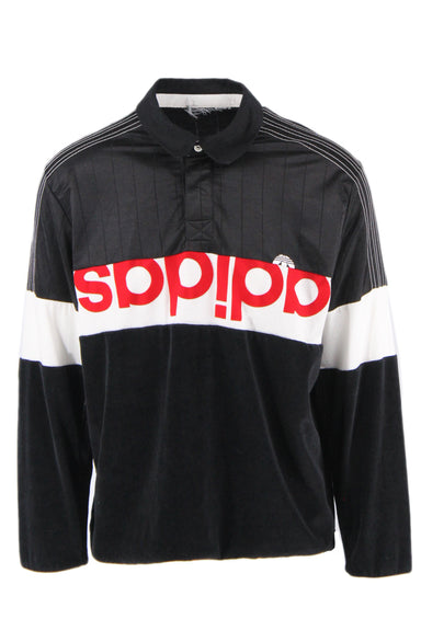 adidas black pull-over shirt. features white stripe with red upside down 'adidas' text and white logo at mid-section. white topstitching details down sleeves, 3 embroidered upside down tonal logos at back. 3-button lapel, boxy cut. unlined.