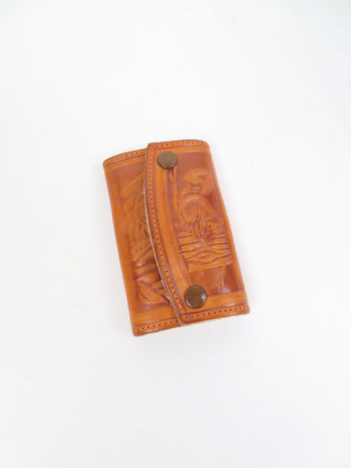 vintage leather key case. features nature scenes on the outside with snap button closure. six key rings on inside.