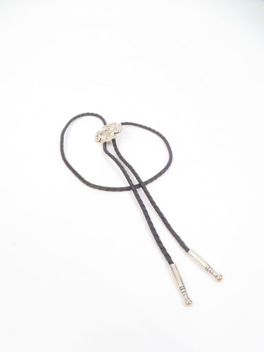 unlabeled black leather bolo tie. features adjustable metal accent slide closure. metal accent aglet tips.