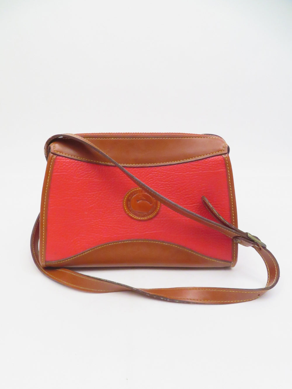 vintage dooney & bourke red and brown crossbody bag. features zippered top closure and adjustable strap.