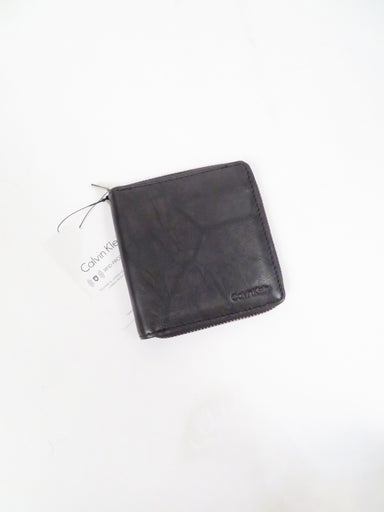 calvin klein black 'zip around slimfold' leather wallet. features 'calvin klein' branding imprinted at front. one currency slot and eight card slots within.