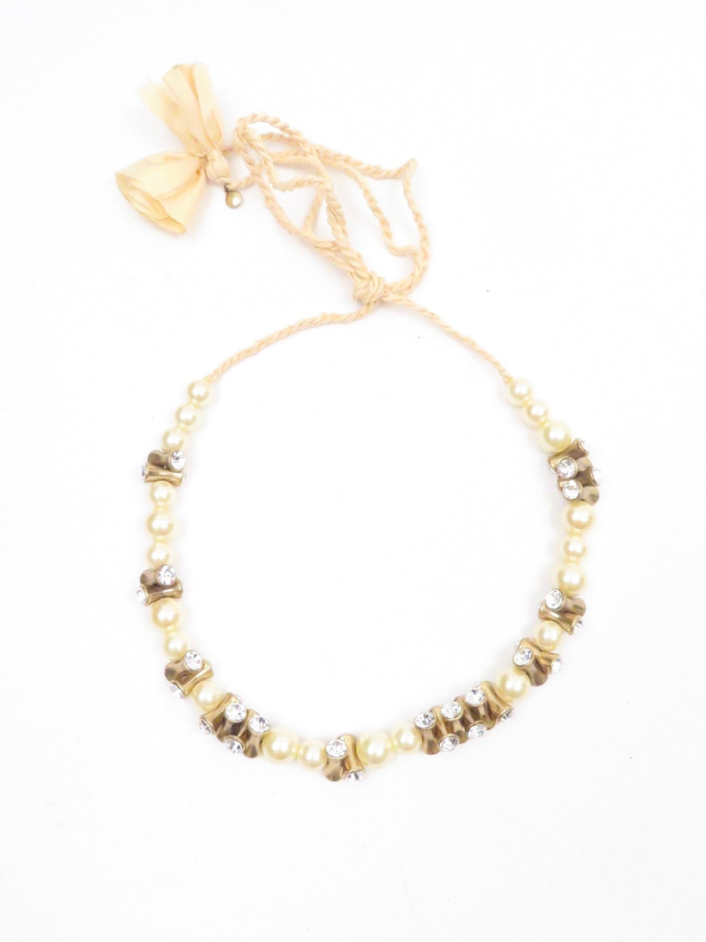 "description: j crew faux pearl rhinestone braided necklace. featuring faux pearl and metal with rhinestone beading. braided ribbon end ties.   color: cream, gold, pearl  size: 53"" length  fabrication: not labeled, unknown meta, rhinestone, possibly silk  condition (all items are secondhand): gently used, pre-owned condition."