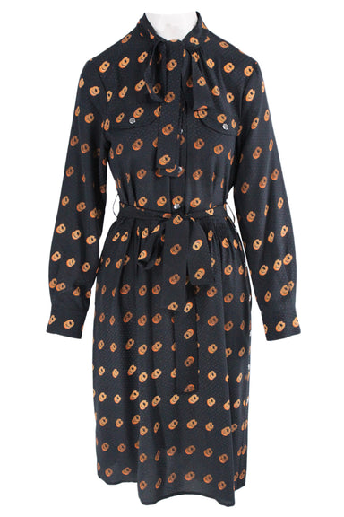 coach black long sleeve print midi dress. features snap button closures along center, side, & sleeves, two buttoned chest pockets, a round neckline, & a belt & belt loops.