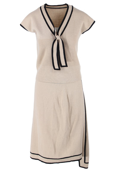 vintage beige two piece. features a short sleeve top with a v neckline and neck tie, and mid length skirt with a subtle asymmetrical design. top and bottom features black contrast stitching. top and bottom appear to be slightly different sizes- please refer to measurements. sold as two piece.