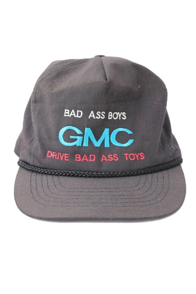 "vintage otto black ""gmc"" hat. features black exterior with ""bad ass boys"" ""gmc"" ""drive bad ass toys"" embroidered multicolored text."